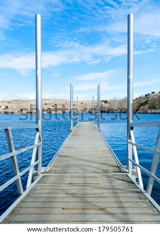 wooden pier on lake with blue sky saturated - stock photo