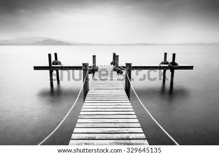 Wooden pier on the lake. Fog. Long exposure. Black and White. - stock photo