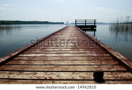Wooden pier on the lake with stone - stock photo