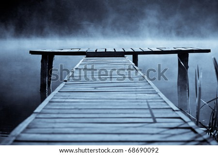 Wooden pier on the mountain river or lake in autumn morning - stock photo