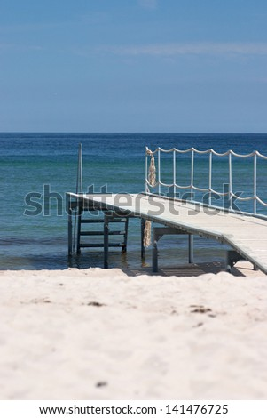 Wooden pier on the sandy beach over the green sea - stock photo