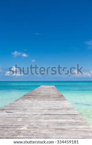 Wooden pier on tropical beach with turquoise water
