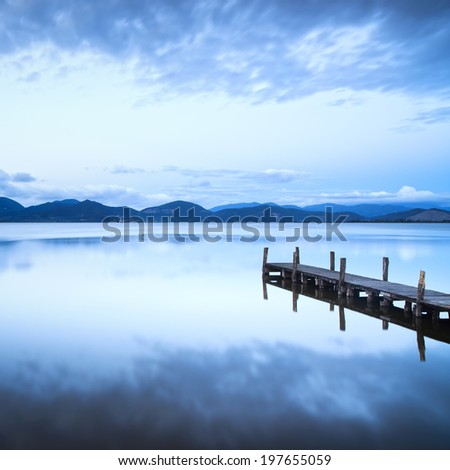 Wooden pier or jetty and on a blue lake sunset and cloudy sky reflection on water. Long exposure, Versilia Massaciuccoli Lake, Tuscany, Italy. - stock photo