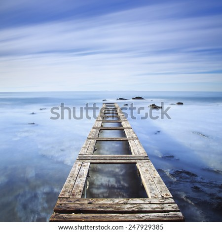 Wooden pier or jetty and rocks on a blue ocean in the morning. Long Exposure - stock photo