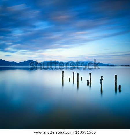 Wooden pier or jetty remains on a blue lake sunset and cloudy sky reflection on water. Long exposure, Versilia Massaciuccoli Lake, Tuscany, Italy. - stock photo
