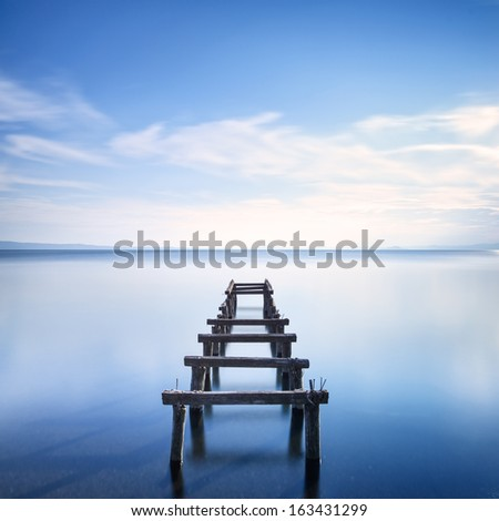 Wooden pier or jetty remains on a blue lake sunset. Long Exposure photography - stock photo