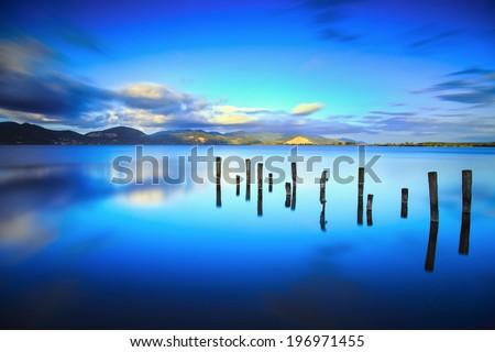 Wooden pier or jetty remains on blue lake sunset and sky reflection water. Long exposure, Versilia Massaciuccoli, Tuscany, Italy. - stock photo