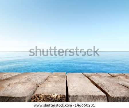 Wooden pier stretching into the blue sea - stock photo