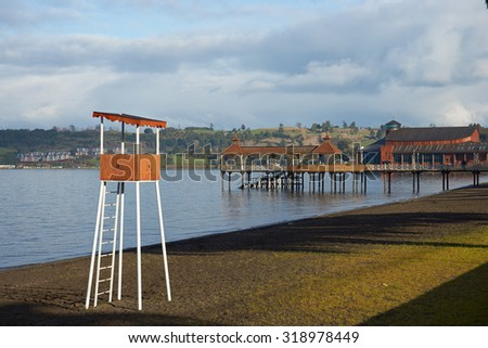 Wooden pier stretching out over the calm waters of Lake Llanquihue in the small town of Frutillar in southern Chile. Lifeguard lookout hut in the foreground. - stock photo