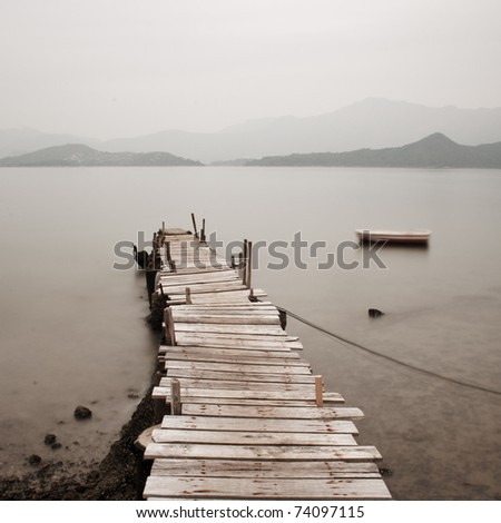 wooden pier with a boat in long exposure, low saturation