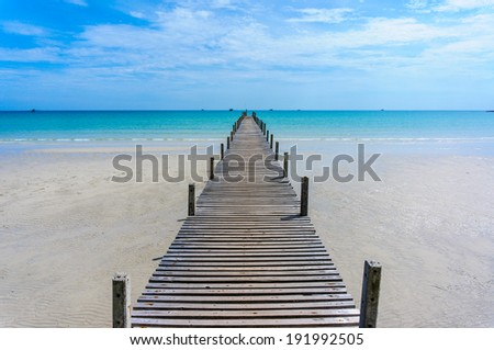 Wooden pier with blue sea and blue sky background - stock photo