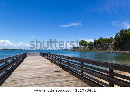wooden pier with old fortification walls in San Juan, Puerto Rico - stock photo