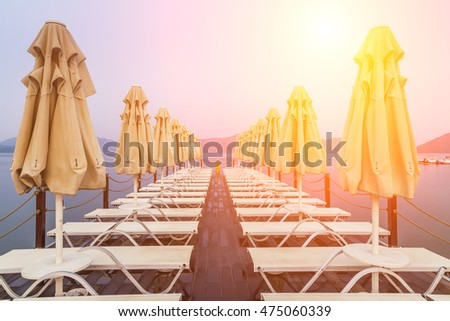 Wooden pier with sunbeds and parasols on the background of sea and mountains.