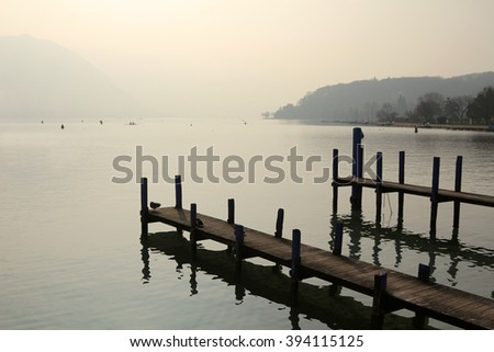 Wooden piers extend into a crystal clear alpine lake, Lake Annecy, in the early morning light. The piers are used by fishing boats to dock in the city of Annecy, France. - stock photo
