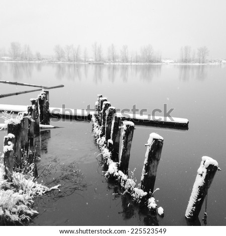 Wooden pillars in a snowy and icy lake surrounded by foliage. - stock photo