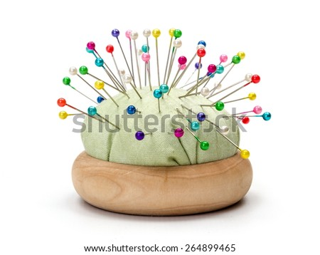 Wooden pincushion full with with colorful pins - stock photo