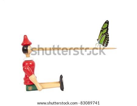 Wooden Pinocchio doll with long nose and butterfly - stock photo