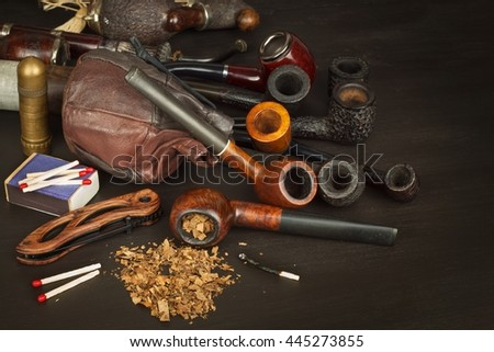 Wooden pipe with tobacco on a black background. Old tobacco pipe and spilled tobacco. - stock photo