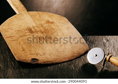Wooden Pizza Paddle Board and Circular Pizza Cutter, Tools of the Trade on Dark Textured Counter Surface - stock photo