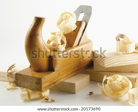 Wooden plane, boards and a shaving on a white background