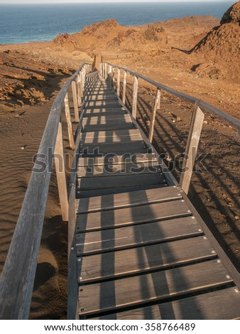 Wooden plank boardwalk with railing climbing uphill to a viewing platform on Bartolome, Galapagos Islands, Ecuador.