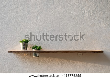 Wooden plank on wall with vase zinc plant, copyspace