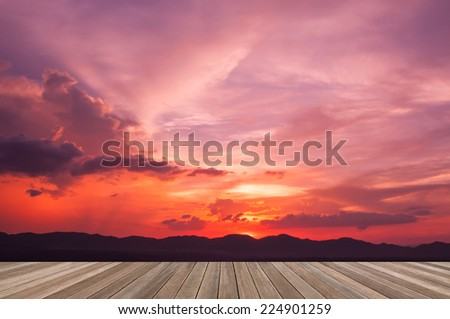 wooden plank platform on silhouette mountains background with beautiful sunset sky - stock photo
