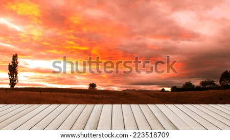 wooden plank platform on the prairie background with awesome morning sky - stock photo