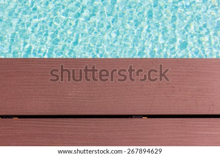 wooden planks at the pool side with vibrant pool water - stock photo