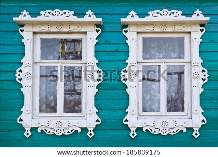 Wooden platbands on two window of an old village house - stock photo