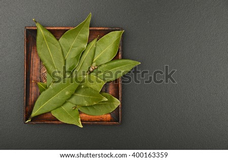 Wooden plate of bay laurel leaves on black chalkboard background