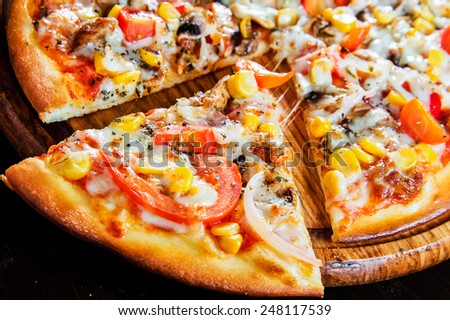 Wooden plate of fresh baked pizza  - stock photo