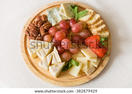 Wooden plate with delicious set of cheeses served with organic grapes, pecans, strawberries and mint. Gourmet snack for celebration or party. Parmesan, camamber, blue cheese. - stock photo