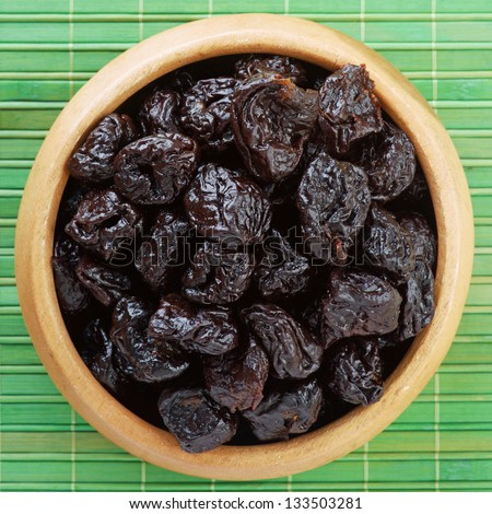 Wooden plate with dried plums, on green bamboo tablecloth. - stock photo