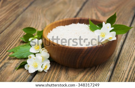Wooden plate with jasmine rice and jasmine flowers on a wooden background - stock photo