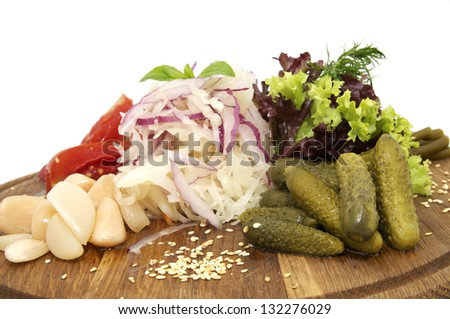 wooden plate with pickles on a white background - stock photo