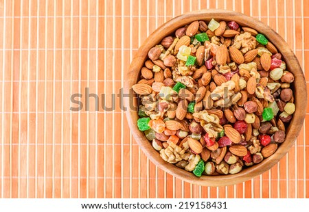 Wooden plate with variety of ingredients - almonds, walnuts, hazelnuts and candied fruit, on bamboo tablecloth. - stock photo