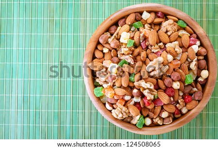 Wooden plate with variety of ingredients - almonds, walnuts, hazelnuts and candied fruit, on green bamboo tablecloth. - stock photo