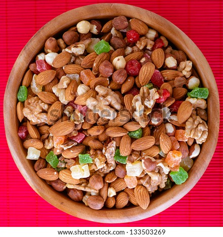 Wooden plate with variety of ingredients - almonds, walnuts, hazelnuts and candied fruit, on red bamboo tablecloth. - stock photo