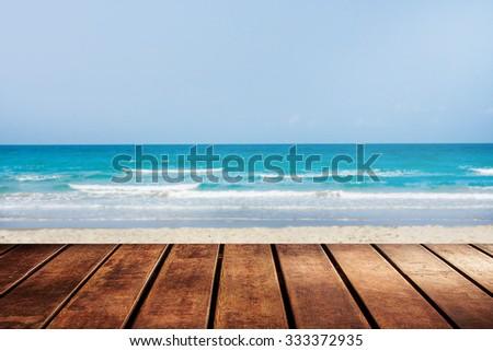 wooden platform beside blue sky beach with palm tree. - stock photo