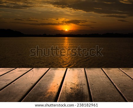 Wooden platform beside lake with sunset  - stock photo