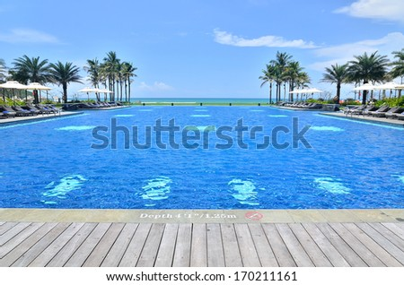 Wooden platform beside tropical resort pool  - stock photo