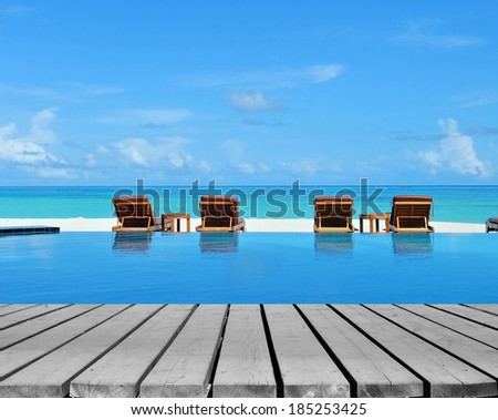Wooden platform beside tropical resorts swimming pool  - stock photo