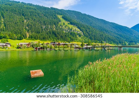 Wooden platform for swimming on green water Weissensee lake in summer landscape of Alps mountains, Austria - stock photo