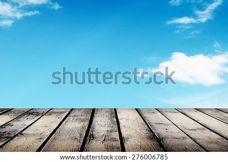 Wooden platform under the blank blue sky in cloud - stock photo