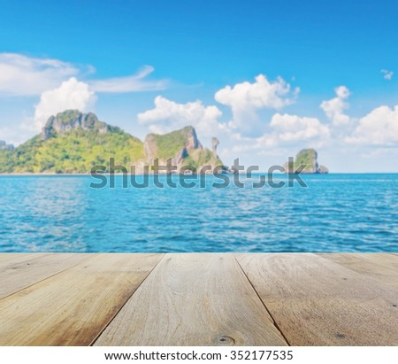wooden platform with blurred beautiful seascape of chicken island (koh kai) in the andaman sea, off the coast of Krabi, Thailand - stock photo