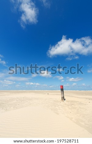Wooden pole at the beach of Dutch wadden island Terschelling - stock photo