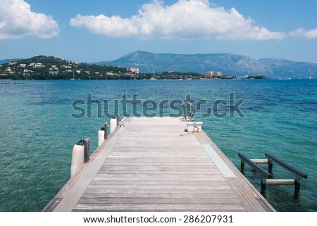 Wooden pontoon stretching into the sea in Greece, Corfu - stock photo