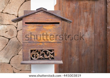 Wooden post box from Thailand with space on wooden door background - stock photo