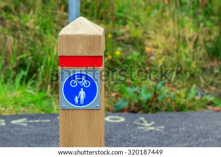 Wooden Post marking pedestrian and cycle path sign - stock photo